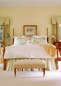 Pale yellow walls set off spring green valances and pillows in this master suite. The windows on either side of the bed are small, but have been given a larger scale with draperies of cotton damask that extend on the sides. The striped bed skirt includes ...