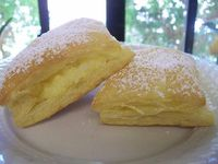 Coconut Pastries -1 package Puff Pastry 3 eggs 1 cup of milk 1 cup of sugar 1 cup of coconut sprinkle of vanilla essence Powdered sugar for garnish