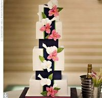"""Beautiful wedding cake with cascading flowers and blue """"ribbon"""" band."""