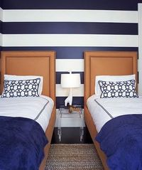 Navy striped walls with orange headboards